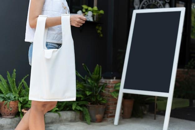 Девушка держит сумку холст ткани на фоне ресторана