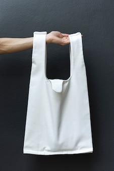 Рука держит сумку холст ткани на черном фоне стены