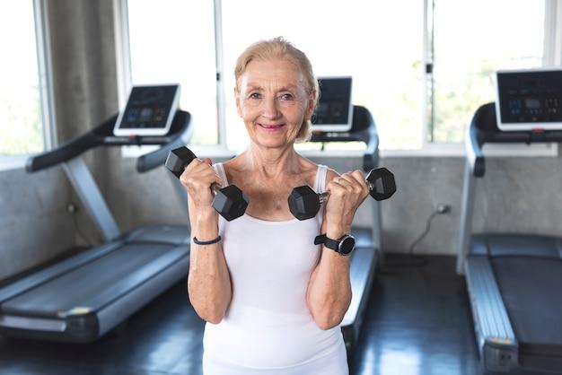 年配の女性運動フィットネスジムでダンベルを持ち上げます。