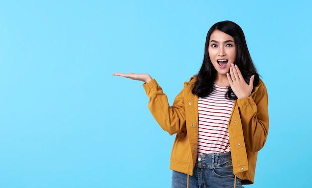 青の背景に分離されたスペースをコピーするために開いた手でアイデアを提示する若いアジア女性ジェスチャー。