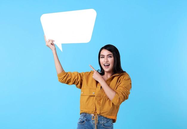 空白の吹き出しを押しながら青い背景上のテキストのための空のスペースで幸せなアジアの女性を笑っています。