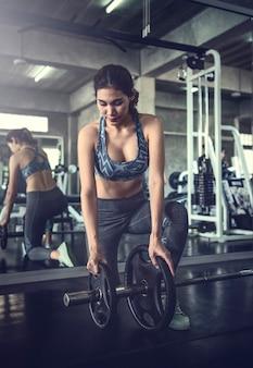 アジアの若い女性がジムでバーベルを持ち上げます。健康的なライフスタイルとトレーニングの動機づけの概念。