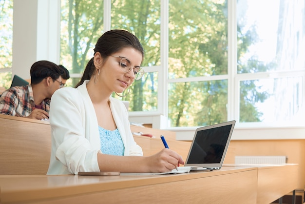 ラップトップを使って大学で勉強している若い学生。