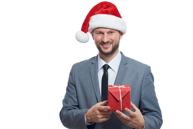 クールなビジネスマン。手に小さな贈り物とポーズをとっているクリスマスの帽子を着てハンサムな男の肖像