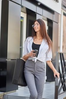 Молодая красивая девушка, перевозящих бумажные мешки, выходя из магазина.