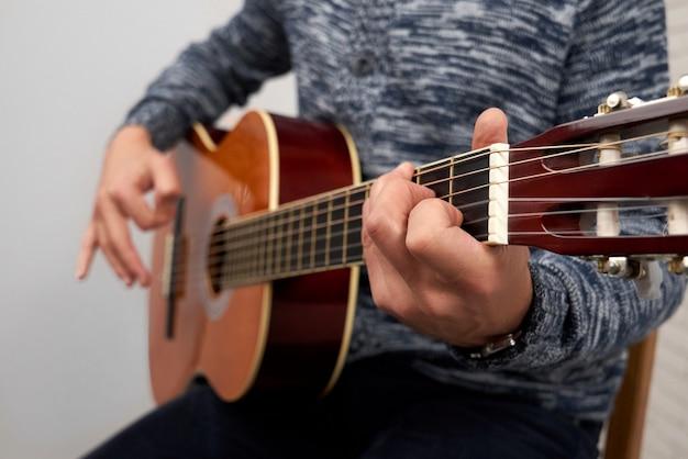 アコースティックギターを弾く男のクローズアップ。
