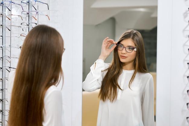 Молодая девушка примеряет очки перед зеркалом.