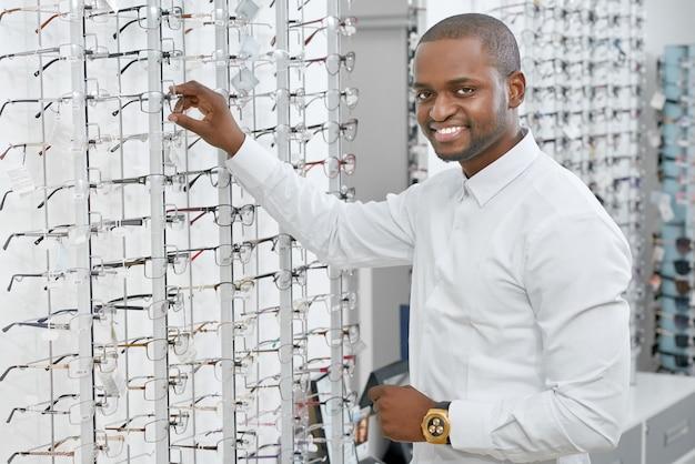 Вид сбоку улыбающийся человек выбирает очки в оптическом магазине.