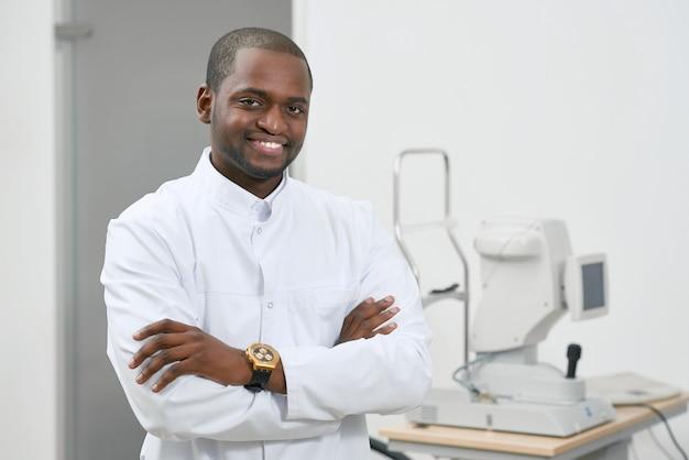 眼科労働で医療機器の近くに立っている笑みを浮かべて男の正面図。自信を持って探している、幸せ。