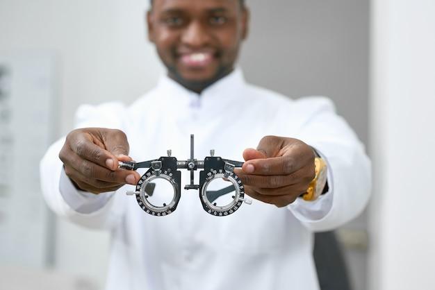 笑みを浮かべて男が白い眼科検査室に立ってみるために医療用レンズを与えること。