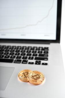 Две золотые биткойны как основные криптовалюты размещены на серебряный ноутбук с размытым графиком на экране на фоне.