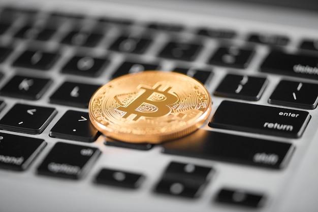 世界の主要な暗号通貨としての黄金のビットコインがノートパソコンのキーボードに置かれました。
