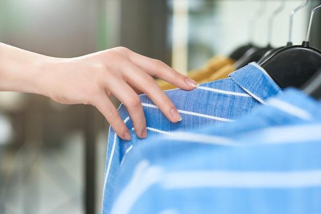 服を着て店のハンガーに横になっている少女の手。