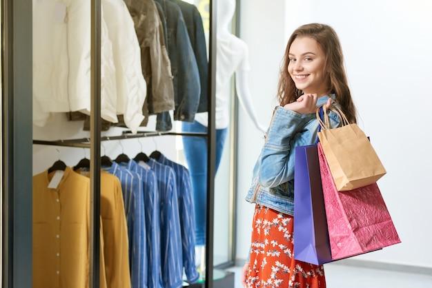 店でバッグやパッケージを保管している笑顔のクライアント。