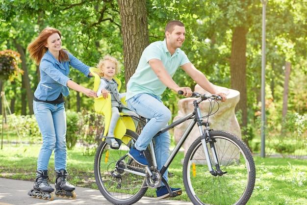 幸せな家族は公園で自転車に乗って