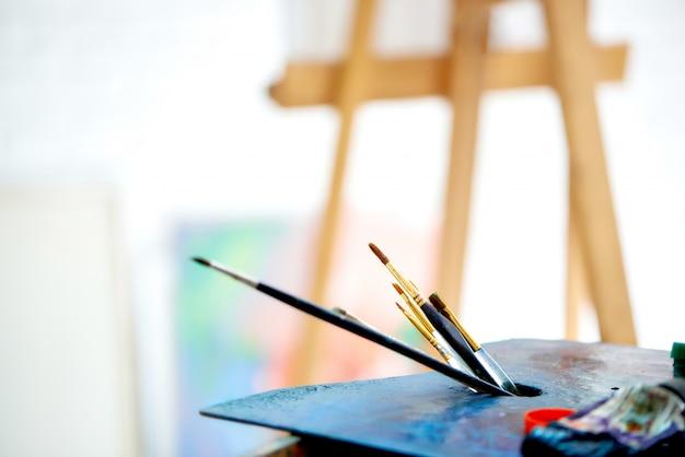 明るいアートスタジオでブラシでパレットのクローズアップ。