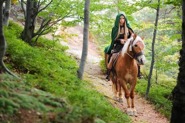 Женский эльф в лесу с лошадью