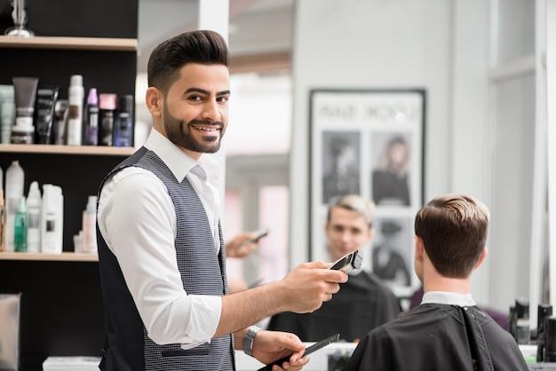 理髪店で若いクライアントの理髪師作るヘアドレスを笑っています。