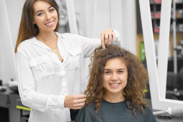 若い巻き毛のクライアントで働いて笑顔の女性ヘアスタイリスト。