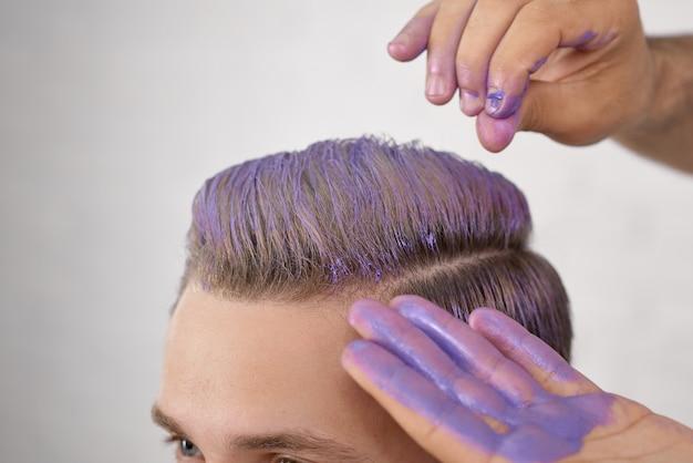 Рука парикмахера, тонирующая волосы молодого клиента в фиолетовом цвете.