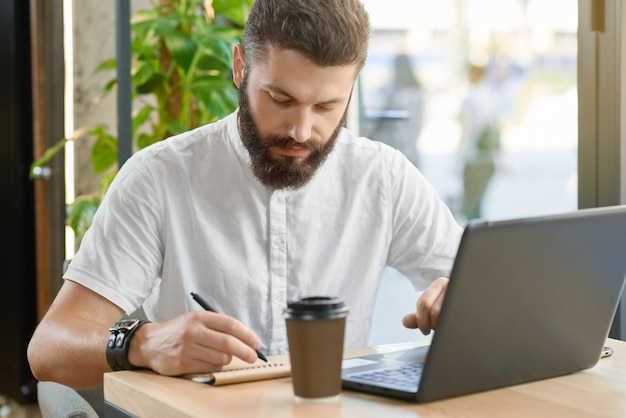 ひげを生やした男がノートを書く、窓のそばに座ってラップトップで作業します。