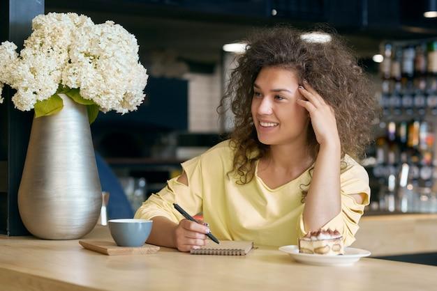 Улыбающаяся кудрявая девушка сидит на деревянный стол, касаясь ее лицо, пить кофе.