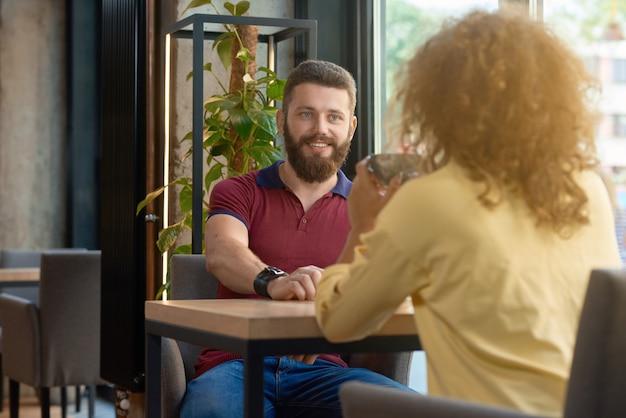 彼のフォントで座っている女の子を見てひげを持つ男の笑みを浮かべてください。