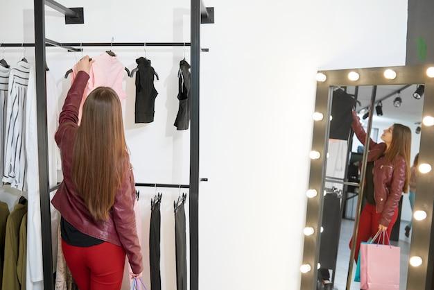 若いクライアントの後ろ姿が店で服を買おうとしています。