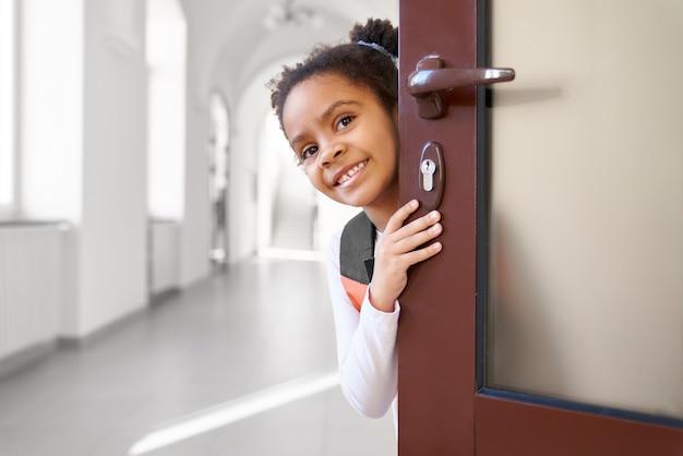 教室のドアから覗くかわいい、ポジティブ、美しい女子高生、笑顔。