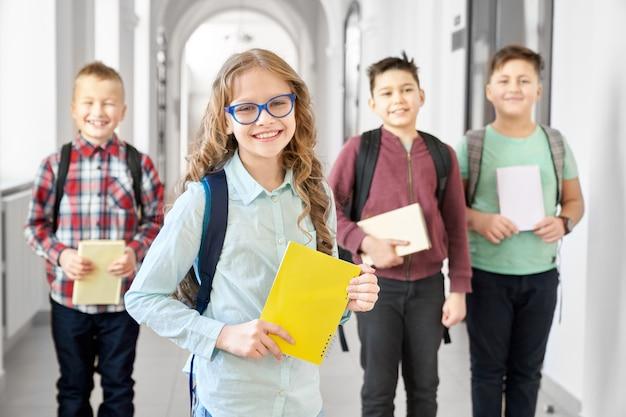 Довольно блондинка школьница в очки, держа в руке желтые заметки и улыбается.