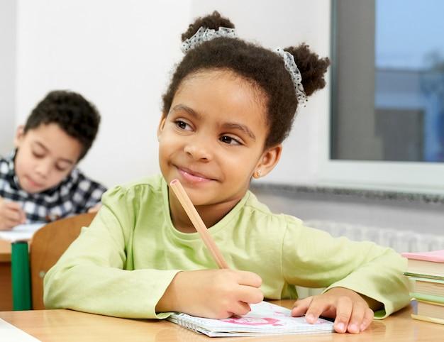 生徒は窓の近くの机に座って、ペンを保持しています。