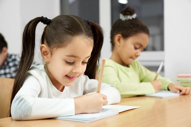 教室の机に座っている小学校のかなり、幸せな女子学生
