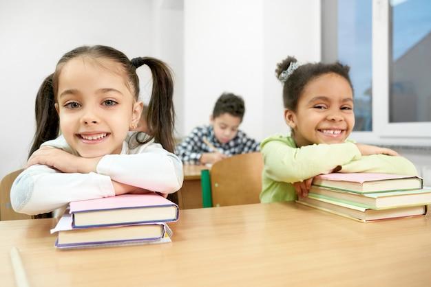 クラスメートは本にもたれ、教室の机にポーズします。