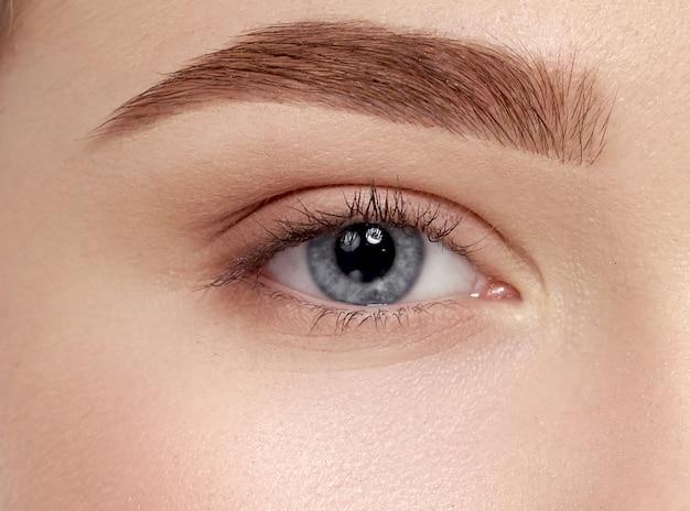 長いまつげと美しい女性の青い目のクローズアップ