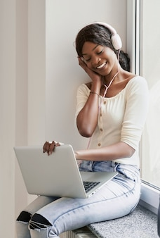 ノートパソコンとヘッドフォンと笑顔のかなりアフリカ系アメリカ人の女の子