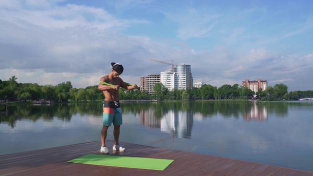 エキスパンダーを使用して腕を伸ばして筋肉男と湖の桟橋