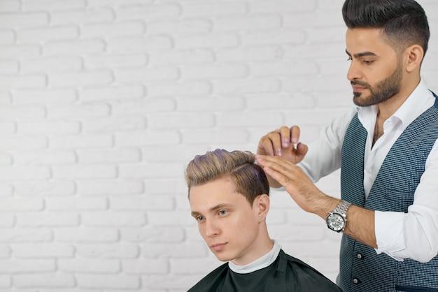 Парикмахер делает сиреневый окрас волос для молодого красавца клиента.
