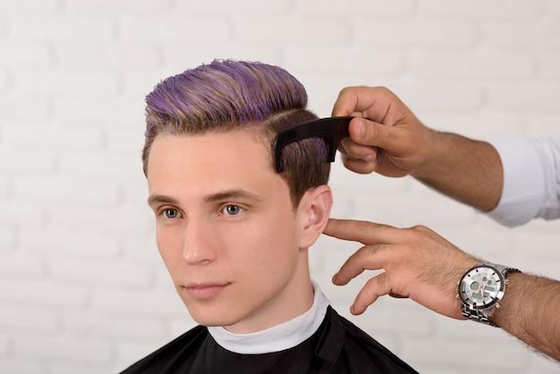 プロの床屋の髪でバイオレット色のトーンを持つ少年。