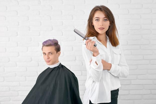 クライアントの前に立っているカメラを見て自信を持って女性美容師。