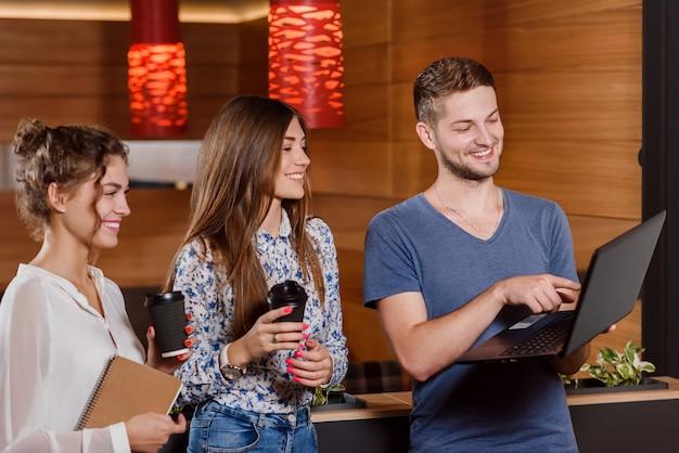 Трое друзей, пить кофе и глядя на экран ноутбука.