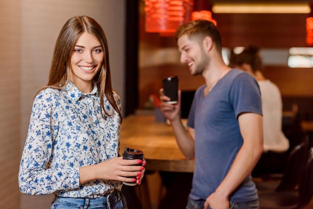 一杯のコーヒーと彼女の写真を撮る男を保持している豪華な女性。