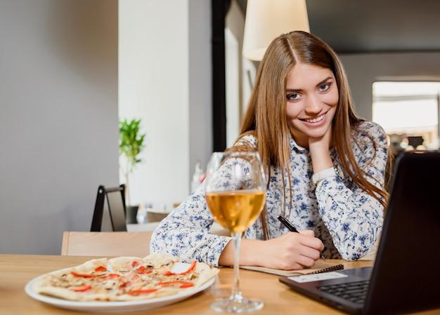 Шикарная женщина работая с тетрадью в ресторане.