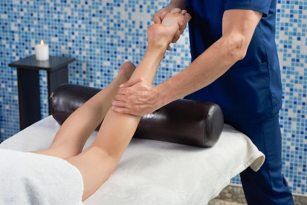 Массажист массажа икроножных мышц и ног женщины в спа