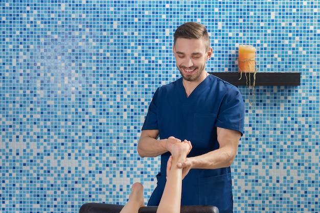 Вид спереди мужской доктор делает массаж ног в спа салоне