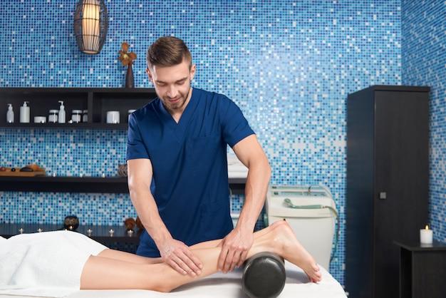 Вид со стороны врача, массирующего икроножные мышцы клиента