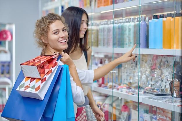 店でカメラ目線の買い物袋と笑顔金髪の側面図