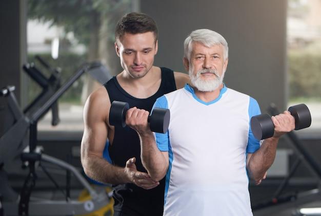 Пожилой мужчина и тренер позирует с гантелями в тренажерном зале.