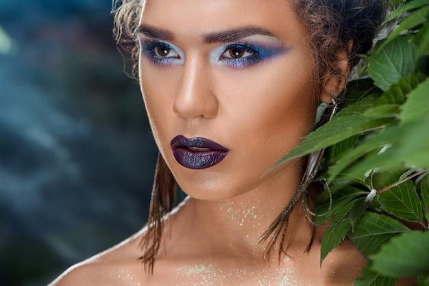 Соблазнительная девушка с яркими цветными макияж и серьги павлиньи перья, глядя в сторону.