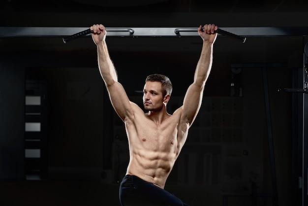 側を見て裸の胴体で運動をしている少年。