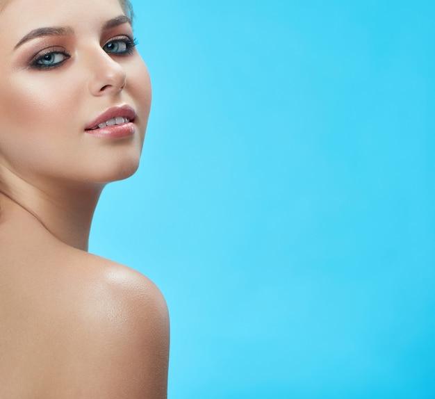 プロのメイクアップと完璧な眉を持つ金髪の女性。